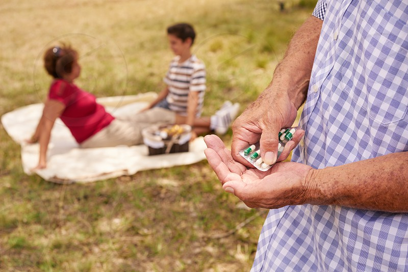 Old people senior couple elderly man and woman in park. Sick grandpa taking prescription drugs medicine pills for heart care illness disease photo