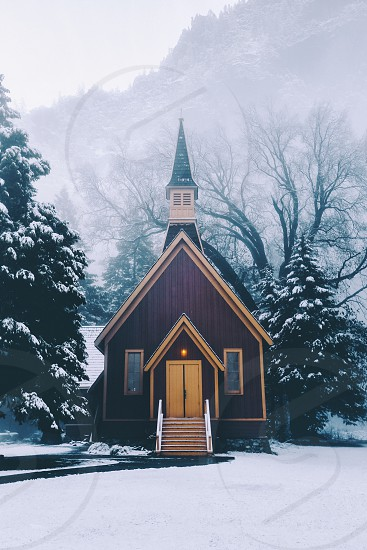 brown and yellow wooden chapel surrounded with mist photo