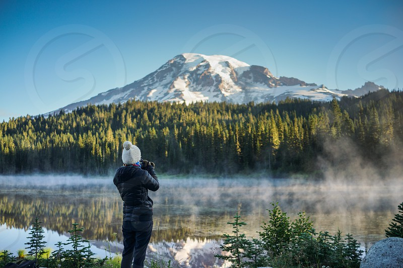 The woman photographer is taking pictures of the mountain and lake at Reflection Lakes and Mount Rainier National Park Washington. photo