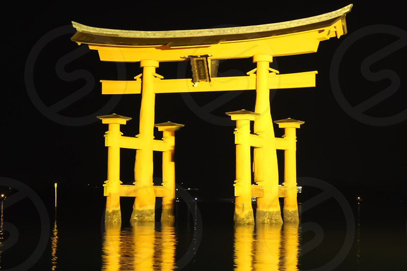 yellow torii gate surrounded with water photo