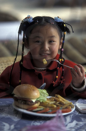a girl with a hanburger in a restaurant in the town of Yangshou near the city of  Guilin in the Province of Guangxi in china in east asia.  photo