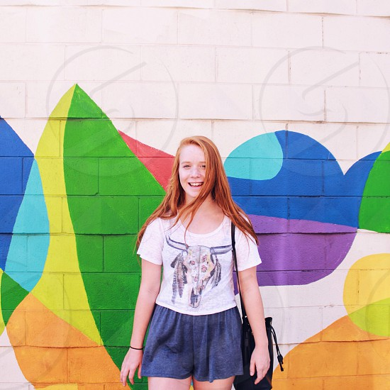 smiling woman in white crew neck thisrt and black shorts with black leather sling bag in front of wall during daytime photo