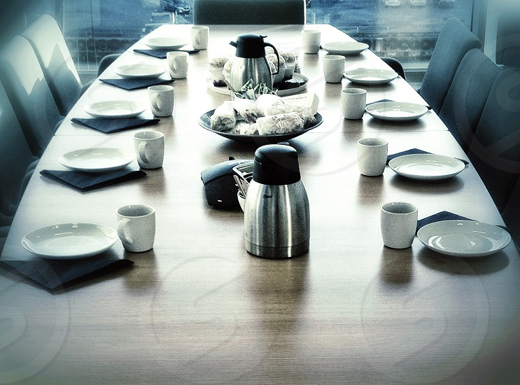stainles steel kettle white plates and cups on table photo