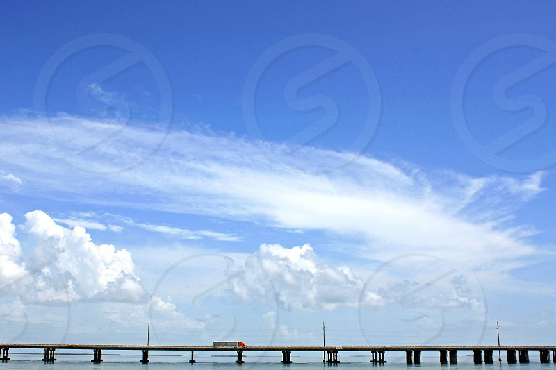 Am 18 wheeler truck is seen alone in the distance crossing the ocean on a long bridge against a blue sky with white clouds. photo