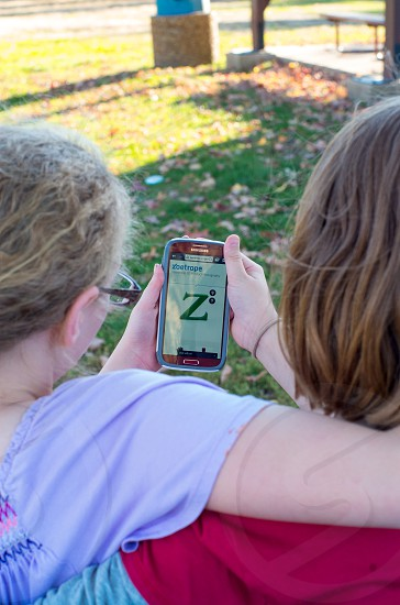2 women holding smartphone photo