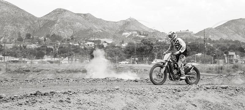grayscale photo of rider riding motocross dirt bike photo