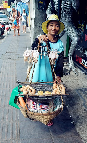 woman with yellow sun hat selling dried squid and bread in a street during daytime photo