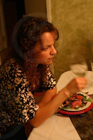 A girl enjoying her dinner time with a simple salad and glass of water photo