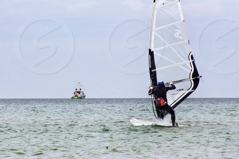 person in black wet suit windsurfing under blue sky during daytime photo