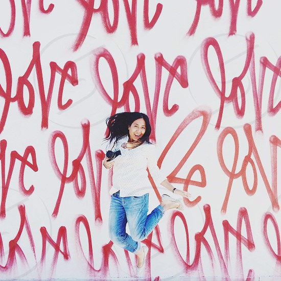 woman jumping in front of graffiti wall  photo