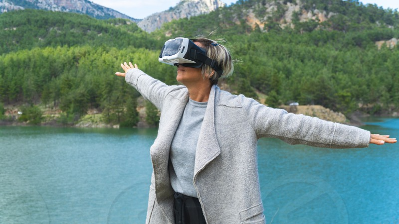 Woman in the nature wearing augmented reality goggles.Adult female having fun with AR glasses on. Flying. Playing. Daytime. photo