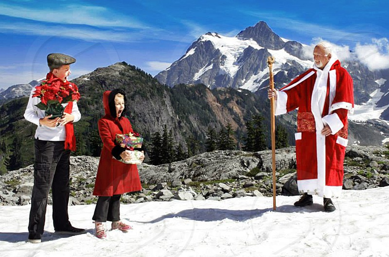 Father Christmas with surprised children in the snowy mountains photo
