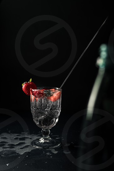 Strawberry infused soda water on a black background photo