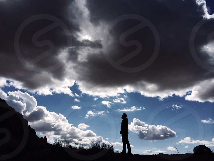 man silhouette under clouds view photo