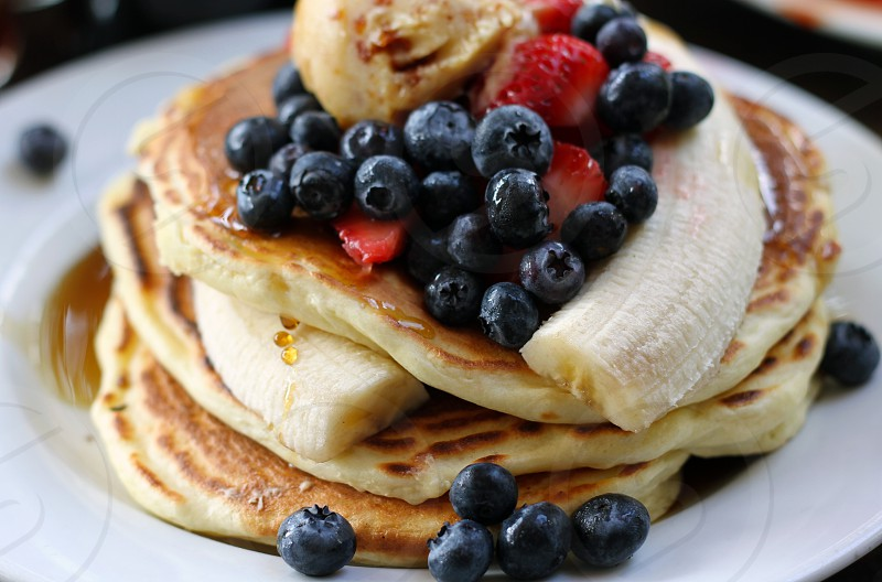 Stack of pancakes with berries and syrup. photo