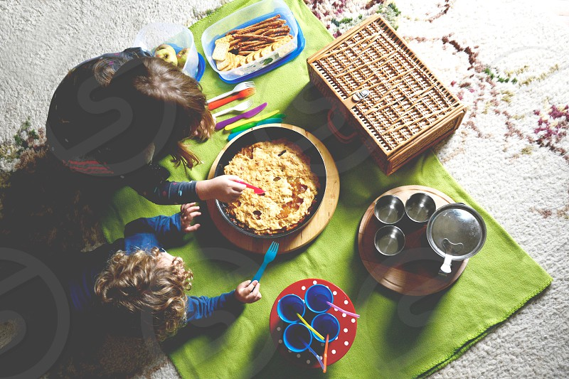 Children enjoying indoor picnic in their living room on the carpet eating snacks and apple pie photo