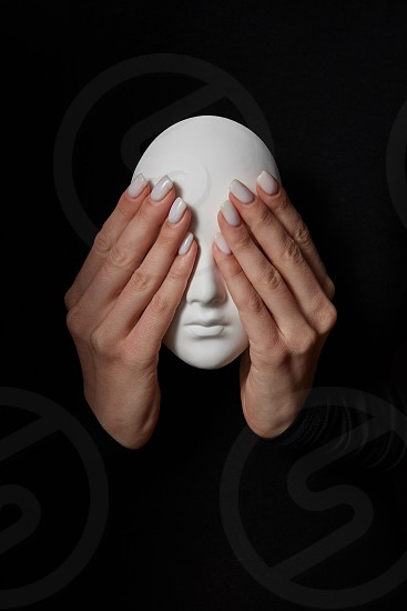 Woman's fingers close eyes of gypsum mask face on a black background. See no evil. Concept three wise monkeys. Place for text. photo