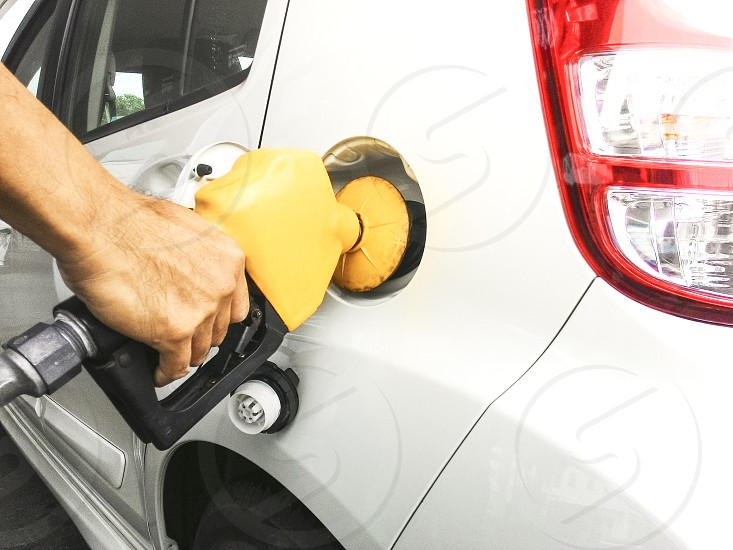 Closeup of hand holding gas pump to refuel car photo