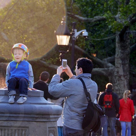 man in grey jacket taking a photograph of a boy in blue vest photo