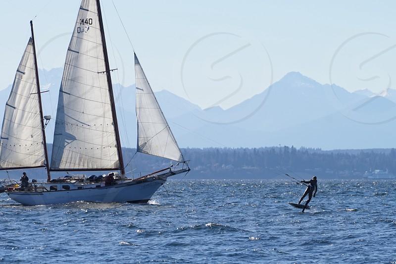 Sailboatclipper shipparaglidersnow capped mountains windyblusteryblue skysunshinecrispwinter photo