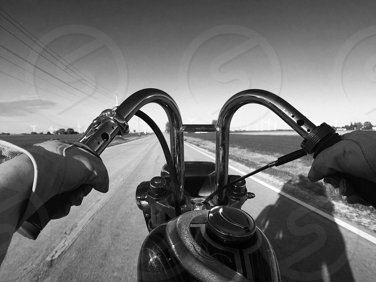 Bike motor road handlespavement gas tank  hands gloves  motorcycle man  arms  painted roadway black white b and w  photo