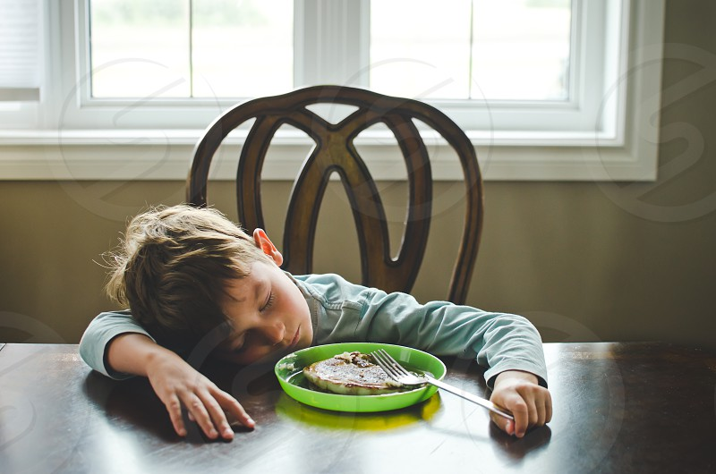 Boy sleeping at the table with his food.  photo