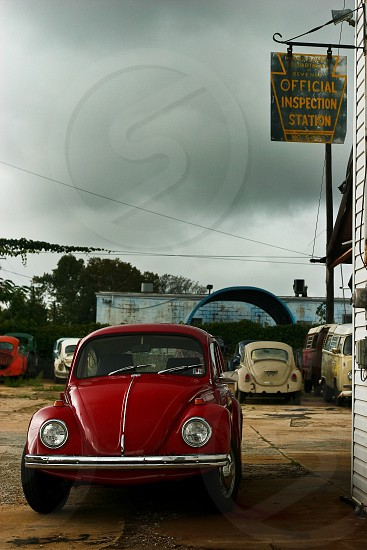 red Volkswagen Beetle in front of Official Inspection Station building photo