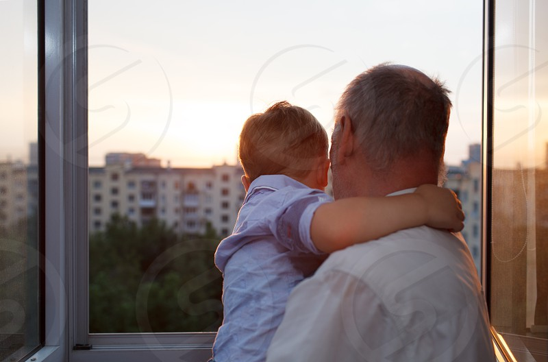 Grandfather holds and embracing grandson on the balcony during sunset photo