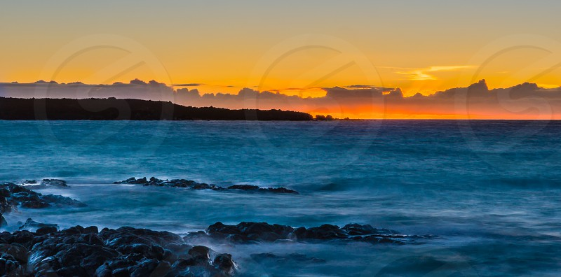 Sunset over the ocean and rocks in Hawaii photo