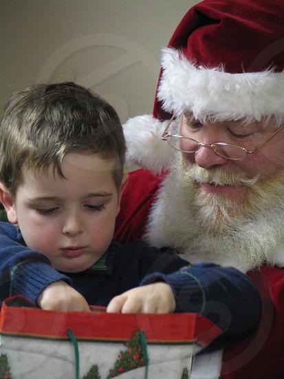 boy peeks in present on Santa's lap photo