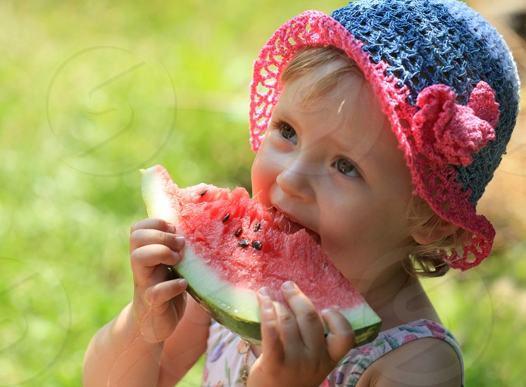 girl in whit tank top eating watermelon fruit photo