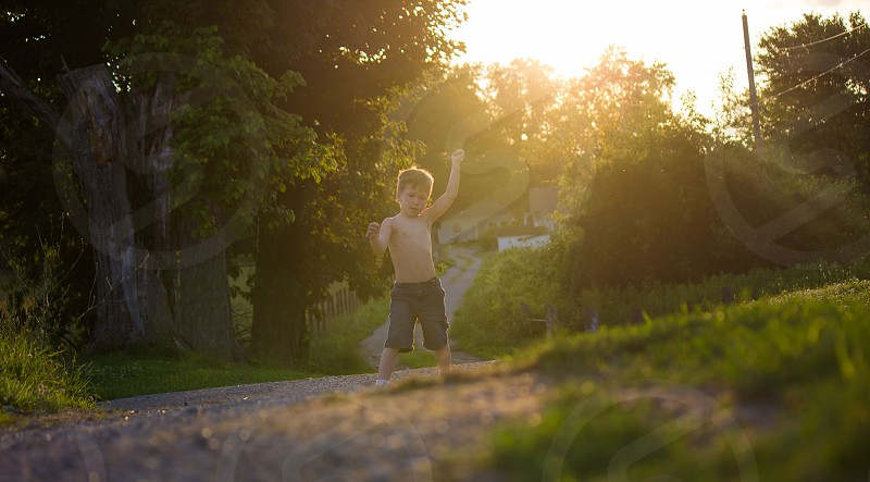 Boy playing in the summer sunset photo