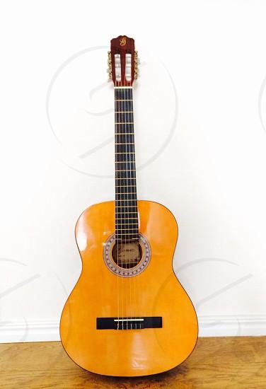 Guitar against a white wall photo