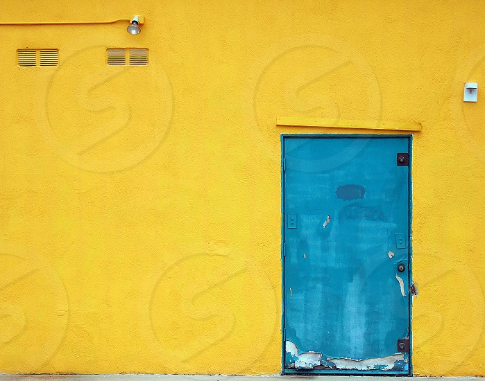 An aqua door on a bright yellow wall has a crooked lintel. photo