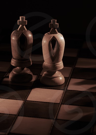 White and black kings on the chessboard opposing each other with copyspace sepia toned photo