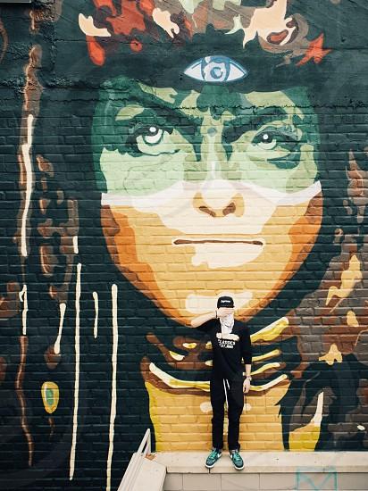 person standing beside graffiti wall photo