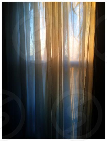 Textiles shiny soft curtains sunrise sunset moody window light blue photo