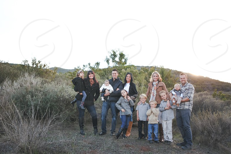 family photo with a background of green and brown leaf trees and grass under grey sky photo