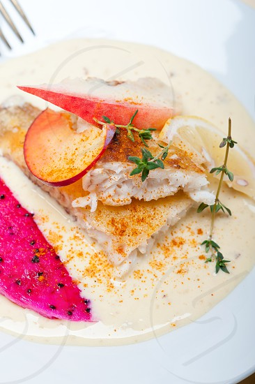 sea bream orata  fillet butter pan fried with fresh peach prune and dragonfruit slices thyme on top photo