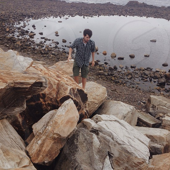 man in black and white sports shirt and green shorts walking on a chunky stone piles during daytime photo