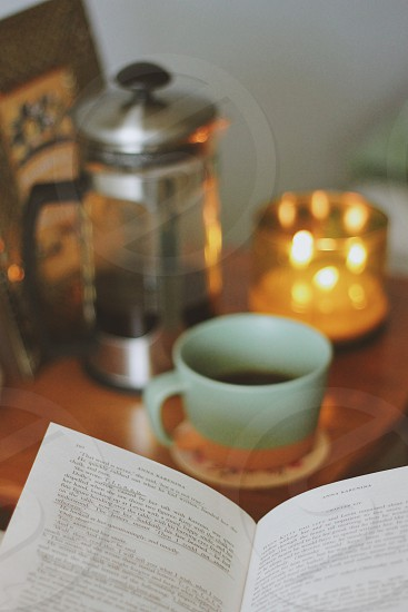 book near ceramic mug on wooden table photo