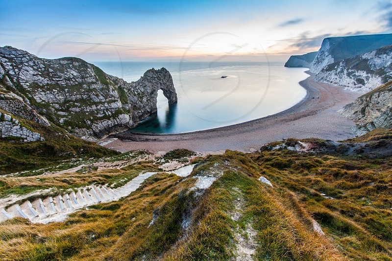 Sunset at Durdle Door on the Jurassic coast of Doset England in the uk featuring a natural geologically formed arch over the sea and steps leading down to the beach photo