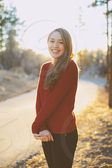 woman wearing red long sleeved shirt standing along the road photo