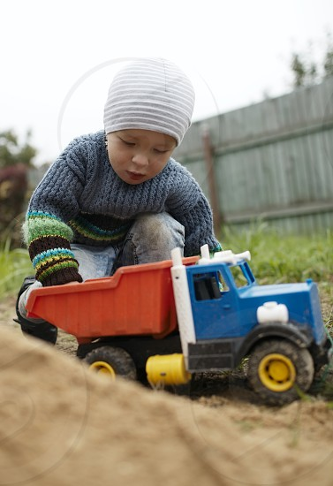 Little boy playing with toy truck rolling it on the sand. Having fun outdoors. photo