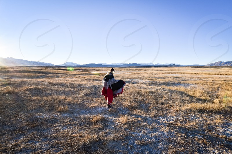 person in red pants standing on brown grass field under white cloudy blue sky during daytime photo