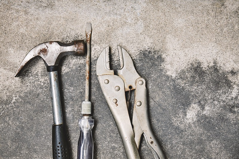Home working tools for repairing Old steel hammer screwdriver and wrench with oxidation on dusty cement background with copy space photo