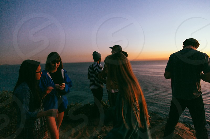 group of people standing beside sea photo