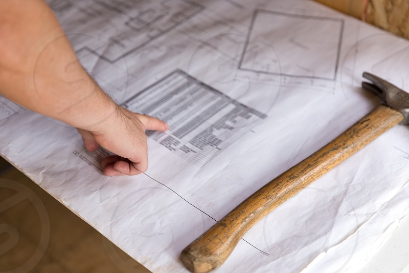 A man reviewing the blueprints of a project photo