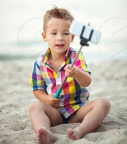 Cute little boy in colorful checkered shirt sitting on the sand and taking picture with smart phone using selfie stick photo