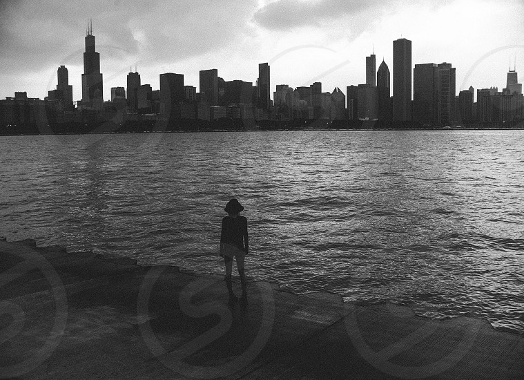 woman in hat standing on concrete at water's edge across bay from city skyline under cloudy sky in black and white photo